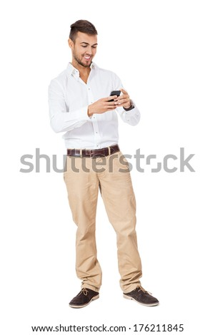 Handsome young man with a beard standing reading a text message on his mobile phone and smiling with pleasure, three quarter pose on white - stock photo