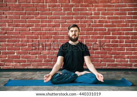 Handsome young man with a beard wearing black T-shirt doing yoga position on blue matt at wall background, copy space, lotus asana, padmasana - stock photo