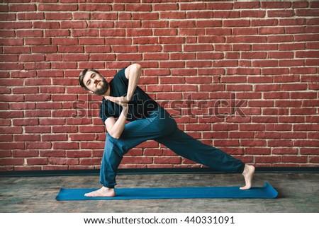 Handsome young man with a beard wearing black T-shirt doing yoga position on blue matt at wall background, copy space, parivritta parshvakonasana asana with namaste mudra. - stock photo