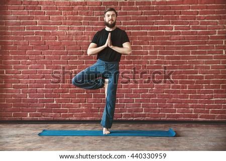 Handsome young man with a beard wearing black T-shirt doing yoga tree position on blue matt at wall background, vrikshasana asana, copy space. - stock photo