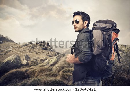 handsome young man with backpack in the mountains - stock photo