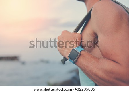 Handsome young man with backpack wearing smart watches near the ocean (intentional sun glare)