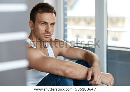 Handsome Young Man With Beautiful Face, Soft Skin And Stubble Beard. Portrait Attractive Healthy Sexy Male Model In White Vest, A-shirt Sitting Indoors. Men Beauty And Man's Health. High Resolution