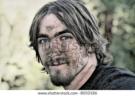 Handsome young man with blue eyes has his face covered with mud after negotiating a particularly muddy ATV trail. - stock photo
