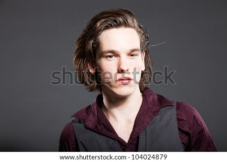 Handsome young man with brown long hair isolated on grey background. Fashion studio shot. Expressive face.