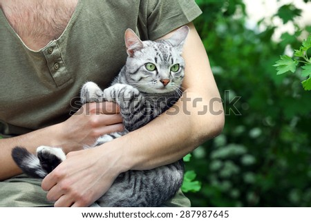 Handsome young man with cute cat outdoors - stock photo