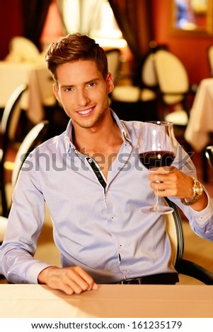 Handsome young man with glass of red wine in restaurant  - stock photo