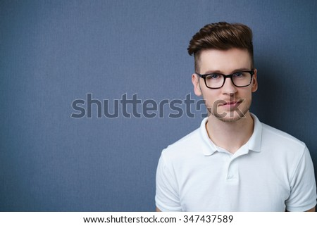 Handsome young man with glasses and a serious thoughtful expression - stock photo