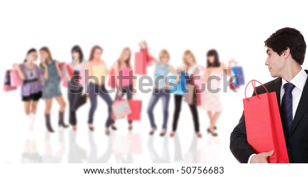 Handsome young man with group of happy cute smiling adult girls with shopping bags on background