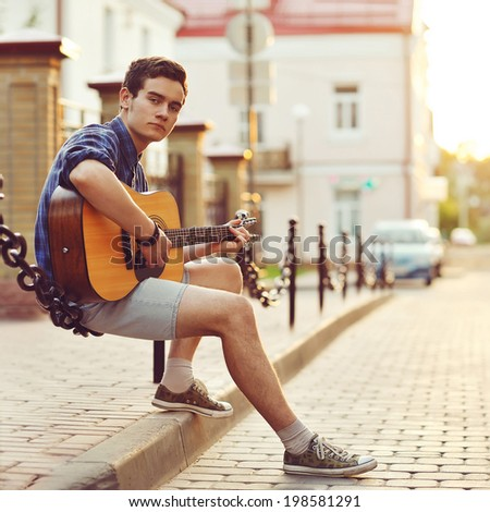 Handsome young man with guitar  - stock photo