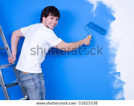Handsome young man with happy smile painting the wall - stock photo