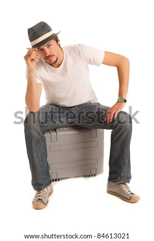 Handsome young man with hat rests on suitcase - stock photo