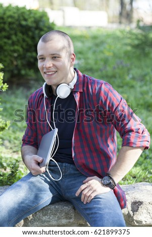Handsome young man with headphones sitting in the park , use tablet and enjoy the outdoors. Selective focus and small depth of field.