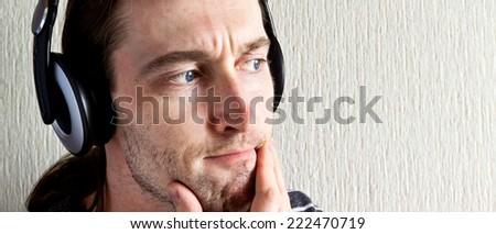 Handsome young man with headphones thinking about music - stock photo