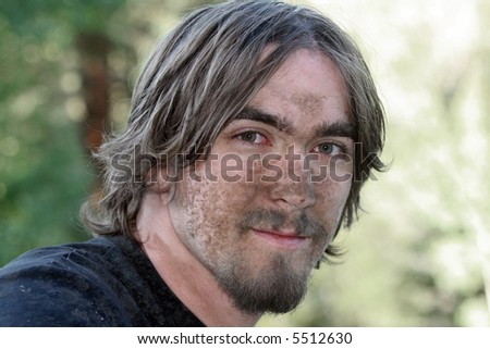 Handsome young man with his face covered with mud after negotiating a particularly muddy ATV trail. - stock photo