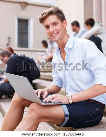 Handsome young man with laptop sitting on a steps outdoors