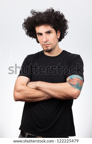 Handsome young man with long curly hair and goatee on a white background. - stock photo