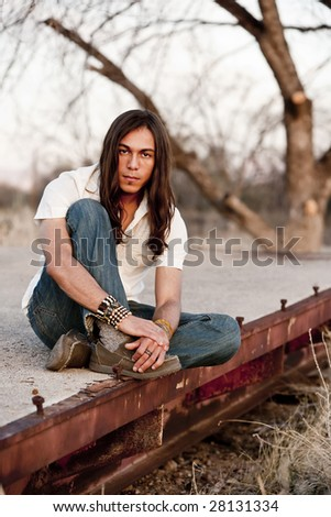 Handsome young man with long hair in an outdoor setting - stock photo