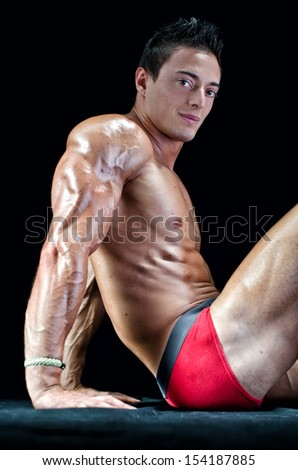 Handsome young man with muscular body, sitting on the floor showing ripped tricep, arm and abs - stock photo
