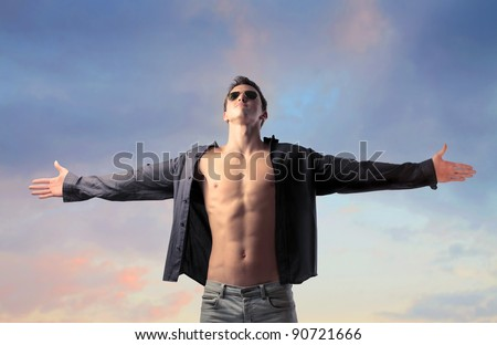 Handsome young man with open shirt stretching out his arms - stock photo