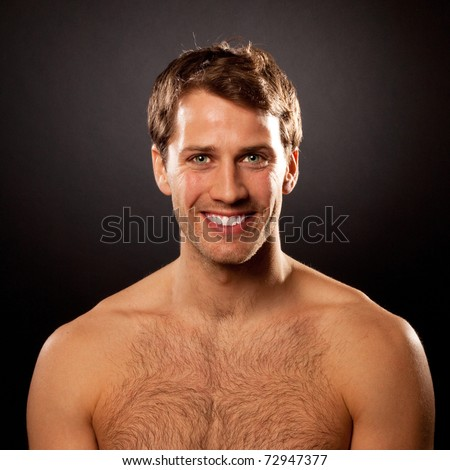 Handsome young man with perfect teeth smiling against dark background