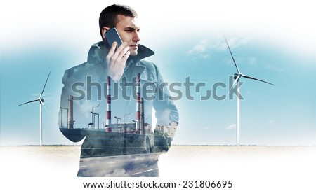 Handsome young man with phone in confrontation between two types of energy - stock photo