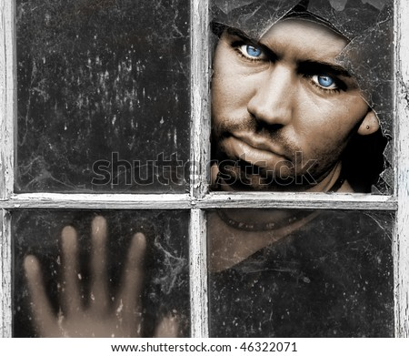 Handsome young Man with piercing Blue Eyes stares through dirty old broken Window with his Hand pressed against the Glass with room for a message above