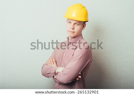 Handsome young man with protective helmet on his head and arms crossed - stock photo