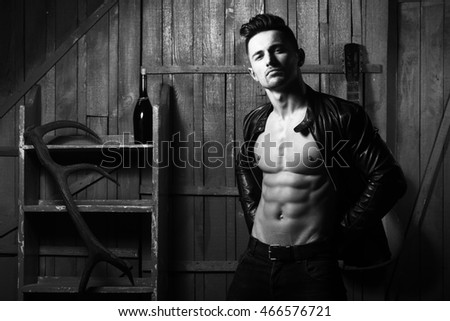 Handsome young man with sexy muscular bare torso in leather jacket standing with acoustic guitar wine bottle and antler on wooden background, black and white