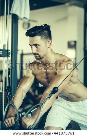 Handsome young man with sexy muscular wet body and bare back training with heavy exercise equipment in gym
