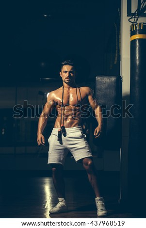 Handsome young man with sexy muscular wet body bare torso and chest holding jump rope