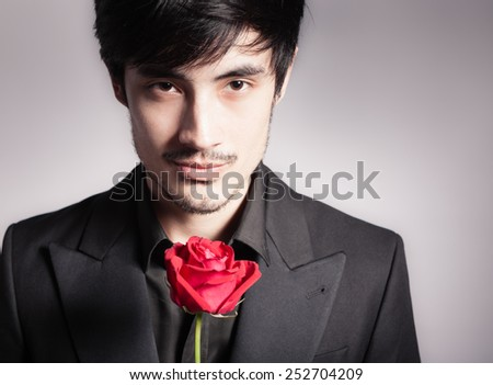 Handsome young man with single rose - stock photo