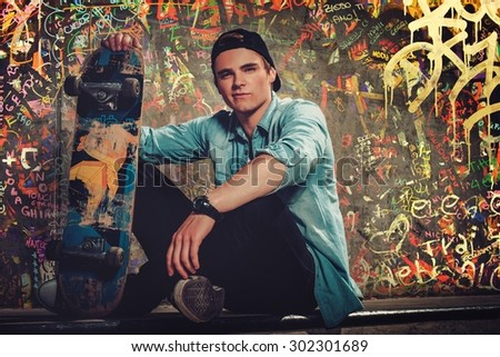 Handsome young man with skateboard outdoors against graffiti painted wall - stock photo