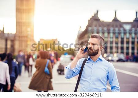 Handsome young man with smart phone on Westminster Bridge - stock photo