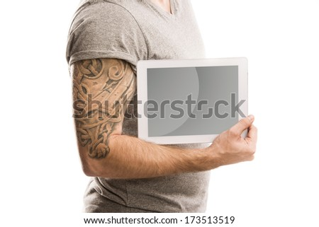 Handsome young man with tattoo is holding digital tablet, isolated on white. - stock photo