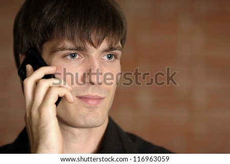 Handsome young man with the phone on a brown background