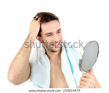 holding a mirror. handsome young man with towel holding mirror isolated on white a
