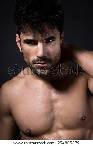 handsome young man with wet hair after shower. fit and muscular bodybuilder showing off his muscles - stock photo