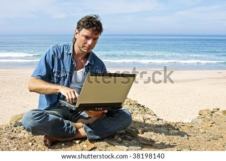 Handsome young man working on his laptop at the atlantic ocean - stock photo