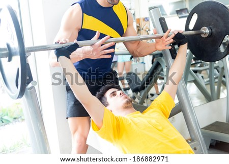 Handsome young man working out at the gym - stock photo
