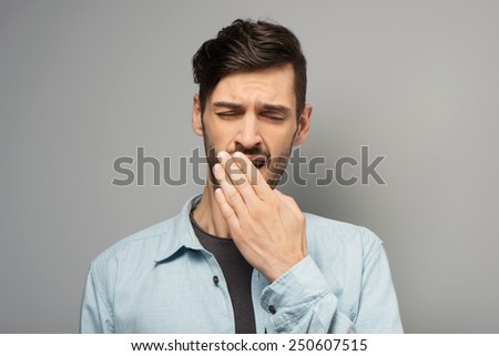 Handsome young man yawning with eyes closed, standing on grey background