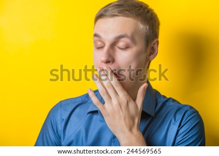 Handsome young man yawns. Close-up portrait. Gesture. Isolated yellow background. photo - stock photo