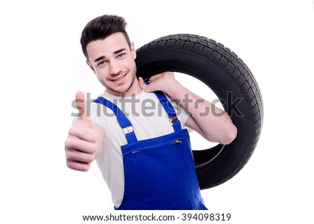 handsome young mechanic holding a tire isolated on white background - stock photo