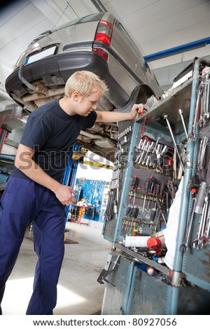 Handsome young mechanic looking at repairing tools in auto repair shop - stock photo