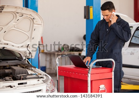 Handsome young mechanic talking to a customer on a cellphone while working on a computer at an auto shop - stock photo