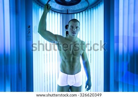 Handsome young men in modern solarium - stock photo