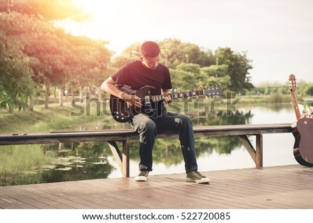 Handsome young men playing guitar in the park. He is wearing a black shirt. Happy and enjoy playing guitar.