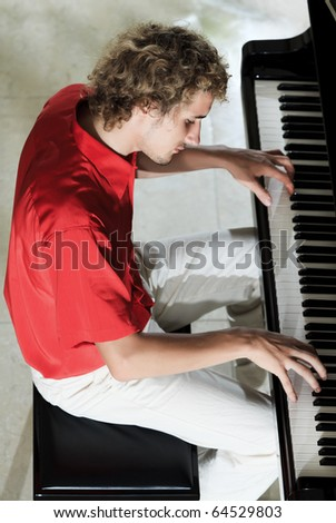 Handsome young men playing piano - stock photo