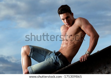 Handsome young muscle man shirtless with hand on rusty metal structure, looking in camera  - stock photo