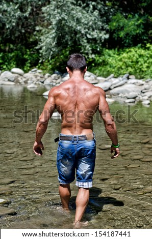 Handsome young muscle man walking in water pond, naked wearing only jeans, seen from the back - stock photo